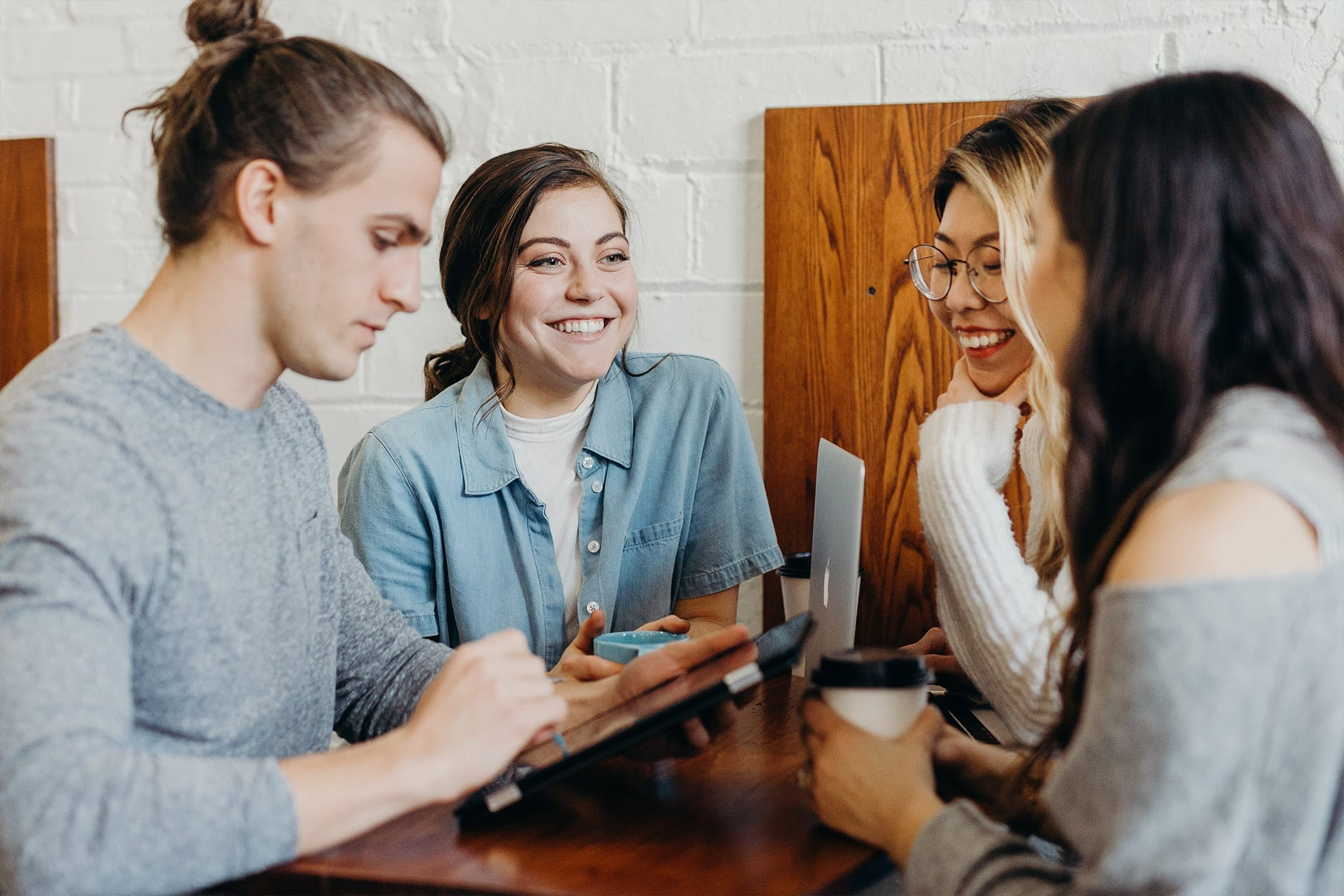 Group of four working at coffee shop table
